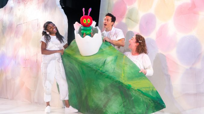 Three actors and a caterpillar puppet